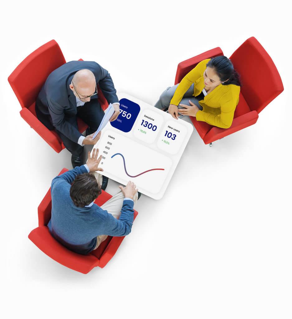 Kolme henkilöä istuu pöydän ääressä, jossa näkyy verkkosivuanalytiikkaa